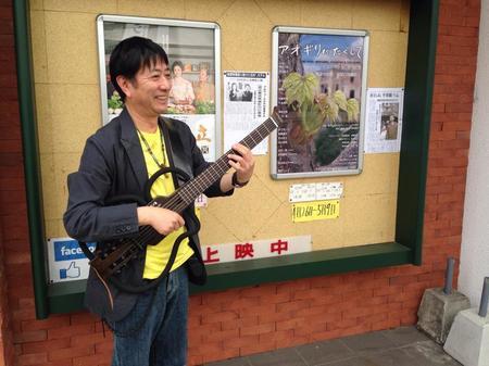 映画館の前でギターを弾くしげ兄.jpg